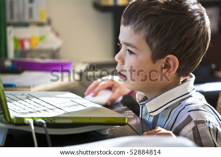 Young boy focused on the computer monitor at his school desk.
