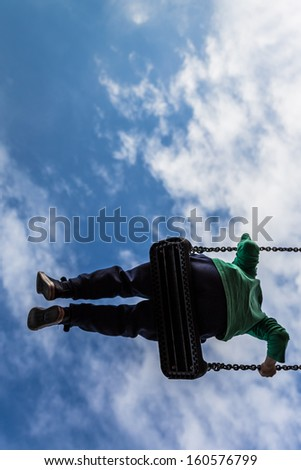 Young boy free in the air on a swing against a deep blue sky with white clouds - stock photo