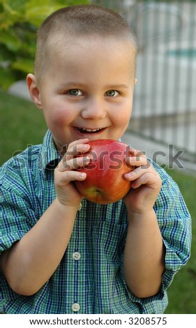 Young boy getting ready to bite into a delicious apple; good concept shot for developing healthy diet habits - stock photo