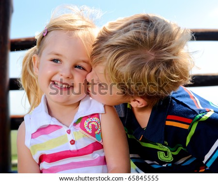 Young boy gives his sister a kiss on the cheek - stock photo
