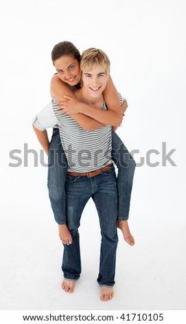 Young boy giving his girlfriend piggyback ride against white background - stock photo