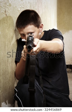 Young boy handling dangerous gun - stock photo