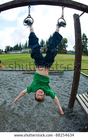 Young boy hanging upside down by his feet at a playground. - stock photo
