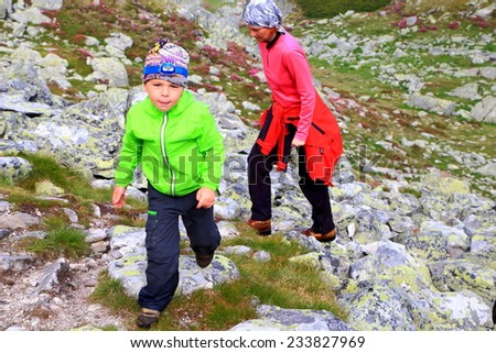 Young boy happy to climb the mountain trail followed by his mother  - stock photo