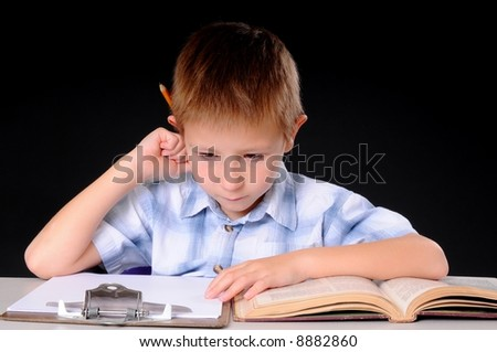 Young boy hard at work studying his books - stock photo