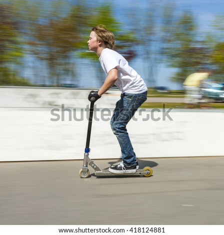 young boy has fun jumping with the push scooter at the skate park - stock photo