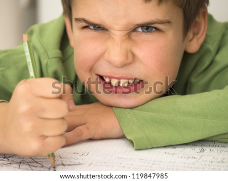 young boy hates doing homework - stock photo