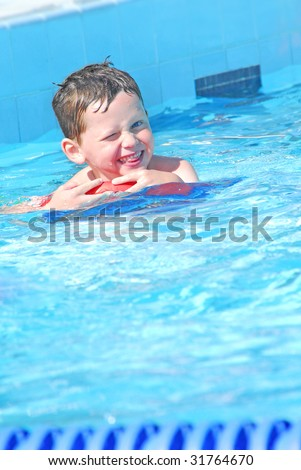 young boy having fun at swimming lesson in pool