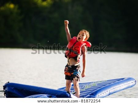 young boy having fun at the lake - stock photo