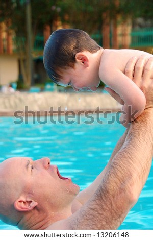 Young boy having fun in pool with dad - stock photo