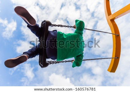 Young boy having fun on a swing against a blue clouded sky - stock photo