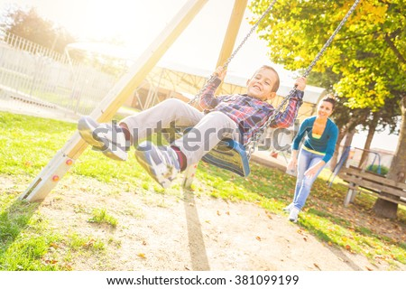 Young boy having fun on the swing. His mother or babysitter his swinging him and they are both enjoying it. Happy family and childhood lifestyle. - stock photo