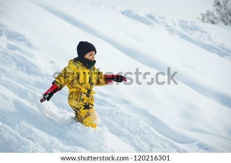 Young boy having fun running in the snow.