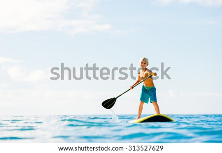 Young Boy Having Fun Stand Up Paddling in the Ocean - stock photo