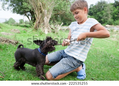 Young boy having fun with his dog outdoors - stock photo