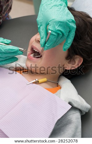 Young boy having his teeth checked at the dentist, doctor holding dental pick and mirror - stock photo
