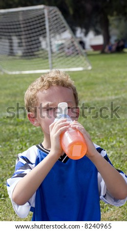 Young boy having orange drink during halftime of soccer game - stock photo