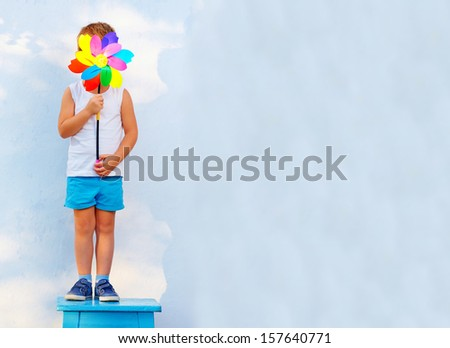 young boy hiding face behind the windmill - stock photo