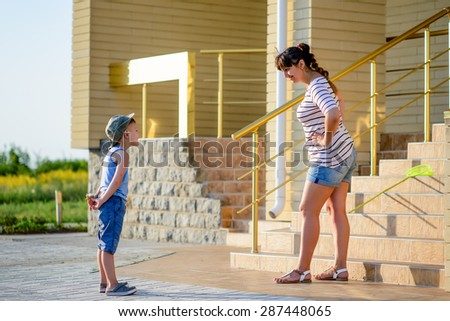 Young Boy Hiding Ice Cream Cone Behind Back While Being Scolded by Angry Mother with Hands on Hips in front of Home - stock photo