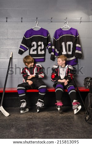 Young Boy Hockey Players Joke as Getting Dressed for Hockey Game - stock photo