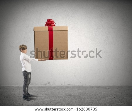Young boy holding a big Christmas present - stock photo