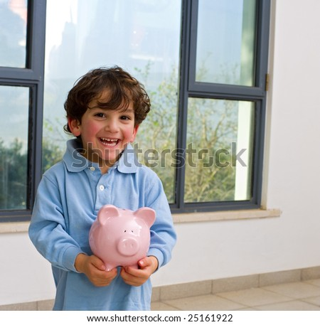 young boy holding a piggy bank - stock photo