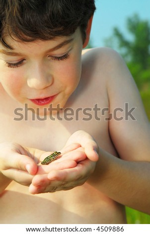 Young boy holding a tiny green frog in his hands