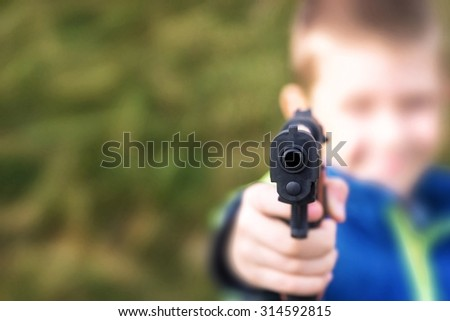Young boy,holding a toy gun,against green grass background. - stock photo
