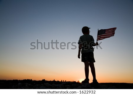 Young boy holding an American flag at sunset. - stock photo