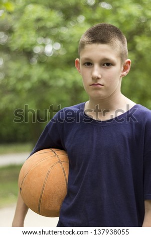 Young boy holding basketball in his hand - stock photo
