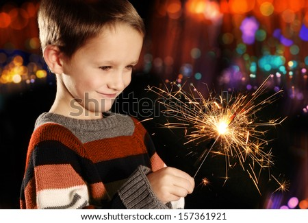 Young boy holding burning sparkler on festive lights background - stock photo