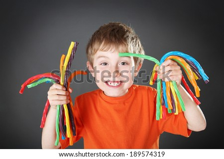 Young boy holding colorful licorice candy - stock photo