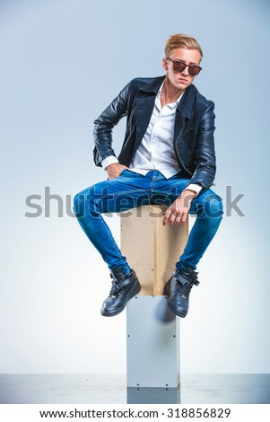 young boy holding his hand in pocket is posing while sitting on boxes with sunglasses on - stock photo