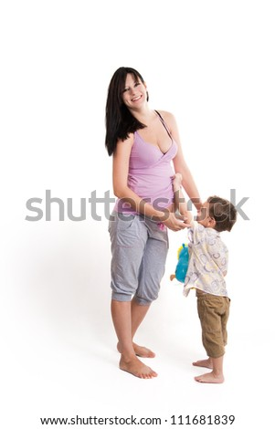 Young boy holding his mother's pregnant belly - stock photo