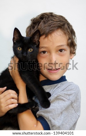young boy holding his pet black cat - stock photo
