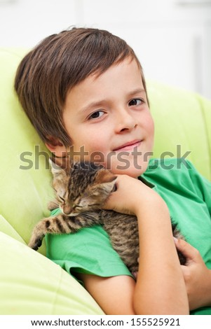 Young boy holding his sleepy kitten - stock photo