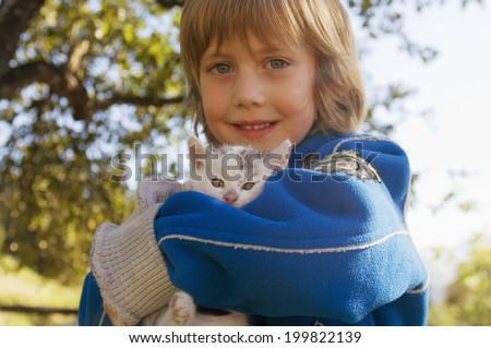 Young boy holding kitten - stock photo