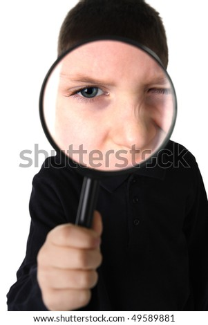 Young boy holding magnifying glass, studio shot isolated on white background - stock photo