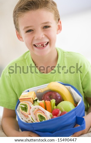 Young boy holding packed lunch in living room smiling - stock photo