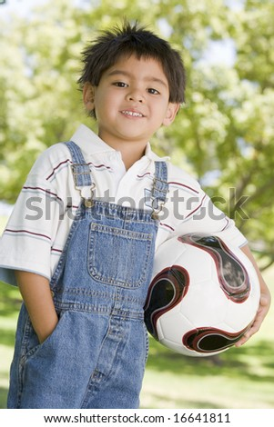 Young boy holding soccer ball outdoors smiling - stock photo