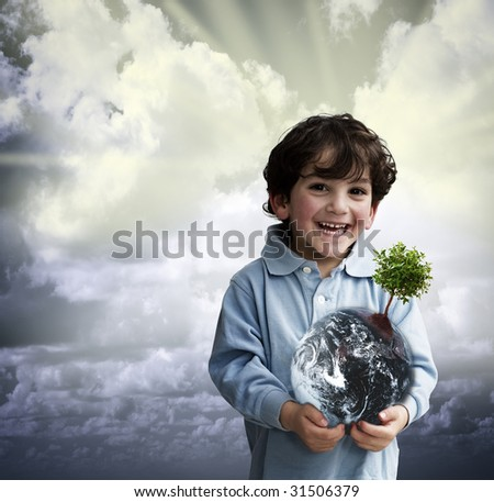young boy holding the globe with a tree on it - stock photo