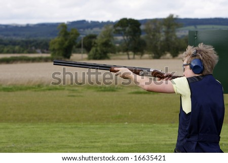 Young boy holding the gun before clay pigeon shooting - stock photo