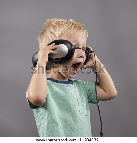 Young boy holds headphones on his ears while he sings.
