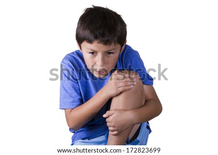 Young boy holds his sore knee - on white background - stock photo