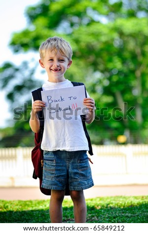 "Young boy holds up handwritten sign ""Back to school!"" - stock photo"