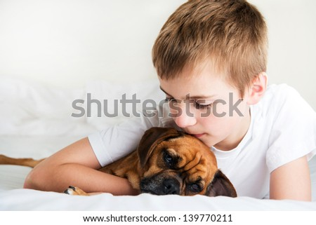 Young Boy Hugging and Kissing his Dog on Forehead - stock photo