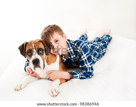 Young Boy Hugging His Dog in Bed - stock photo