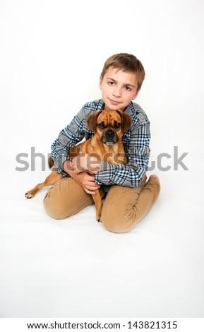 Young Boy Hugging his Puggle Dog - stock photo