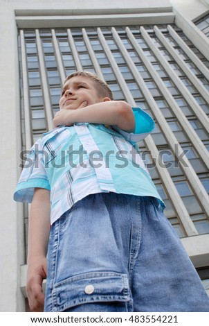 Young boy in a big city. On a background of a skyscraper.