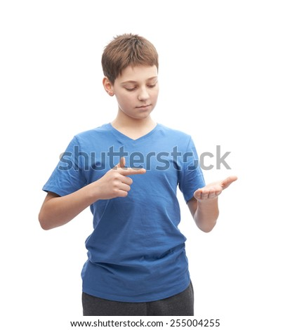 Young boy in a blue t-shirt pointing to a copyspace next to and around him, portrait isolated over the white background - stock photo